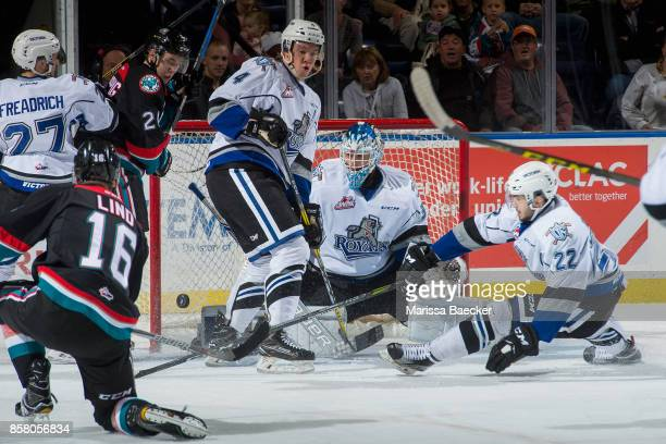 Yan Khomenko tries to block a shot as Griffen Outhouse of the Victoria Royals misses a save on a shot by Kole Lind of the Kelowna Rockets during the...