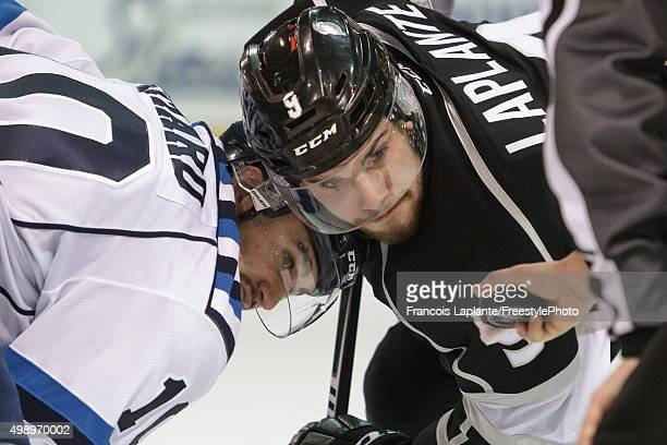 Yan Pavel Laplante of the Gatineau Olympiques and Timothe Simard of the Chicoutimi Sagueneens keep their eyes on the puck during a faceoff during a...