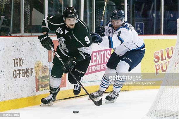 Yan Pavel Laplante of the Gatineau Olympiques controls the puck behind the net against Garrett Johnston of the Chicoutimi Sagueneens on November 27...