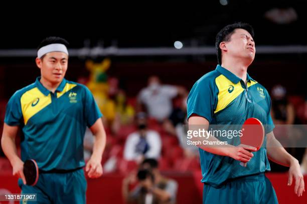 Yan Xin and Hu Heming of Team Australia react during their Men's Team Round of 16 table tennis match on day ten of the Tokyo 2020 Olympic Games at...