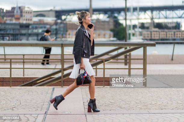 Yan Yan Chan wearing a leather jacket white dress and boots outside Dion Lee during MercedesBenz Fashion Week Resort 18 Collections at Sydney Opera...