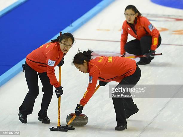 Yan Zhou of China and team mate Qingshuang Yue sweep after Bingyu Wang throws a rock during the Olympic Qualification Torunament match between China...