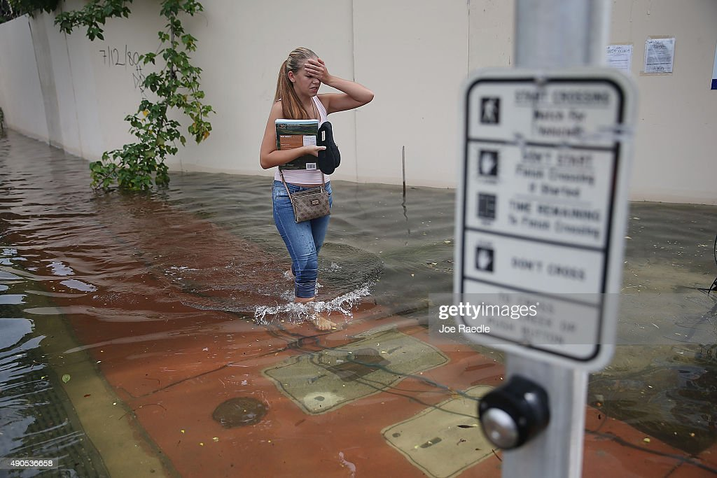 Yana Kibyakova walks through a flooded street that was caused by the combination of the lunar orbit which caused seasonal high tides and what many believe is the rising sea levels due to climate change on September 29, 2015 in Miami Beach, Florida. The City of Miami Beach is in the middle of a five-year, $400 million storm water pump program and other projects that city officials hope will keep the ocean waters from inundating the city as the oceans rise even more in the future.