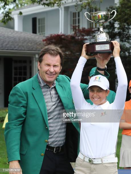 Yana Wilson, the overall winner of the girls 12-13, poses with her trophy and Sir Nick Faldo of England during the Drive, Chip and Putt Championship...
