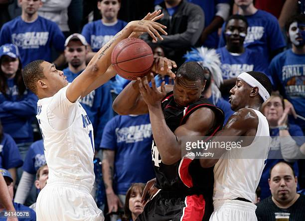 Yancy Gates of the Cincinnati Bearcats loses the ball while being defended by Matt Simpkins and Robert Dozier of the Memphis Tigers at FedExForum on...