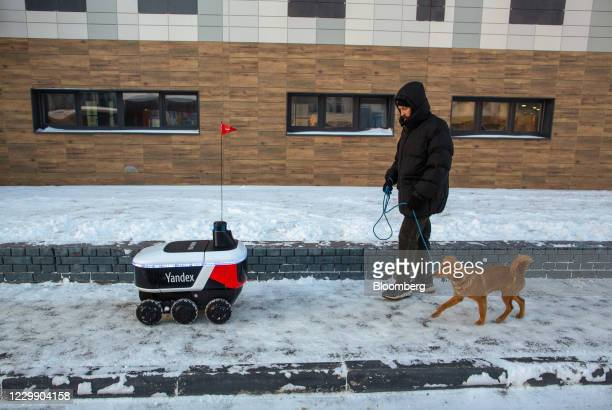 Yandex.Rover autonomous delivery robot passes a dog walker as it transports online food orders to customers in Innopolis, Russia, on Tuesday, Dec. 1,...