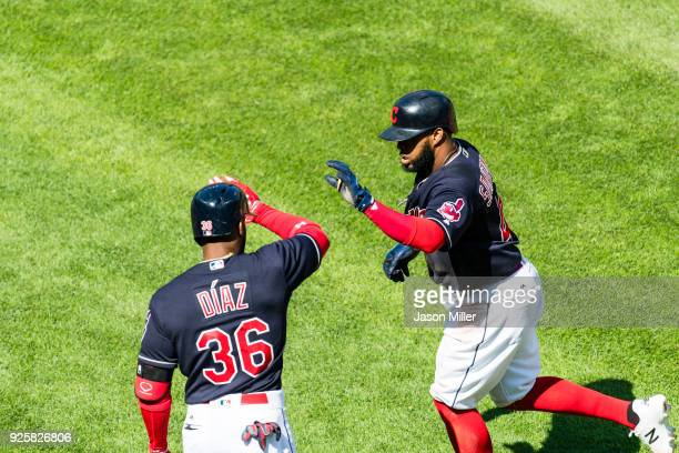 Yandy Diaz of the Cleveland Indians celebrates with Carlos Santana after Santana scores during the fourth inning against the Baltimore Orioles at...