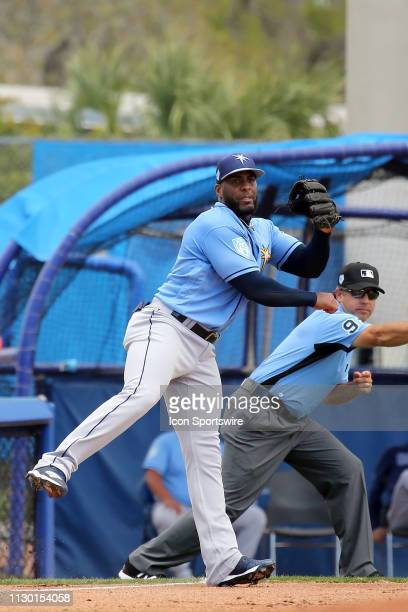 Yandy Diaz of the Rays throws the ball over to first base as third base umpire James Hoye signals fair ball during the spring training game between...