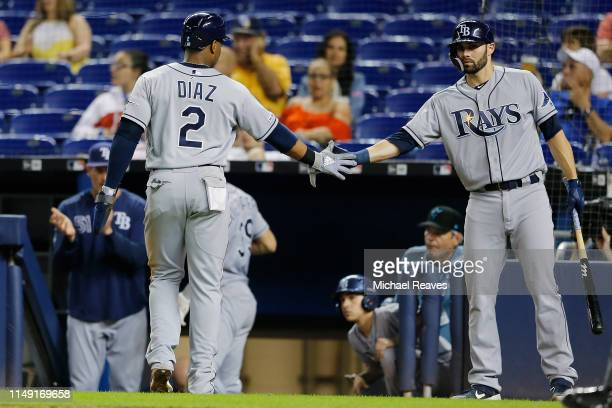 Yandy Diaz of the Tampa Bay Rays celebrates with Anthony Bemboom after scoring a run in the ninth inning against the Miami Marlins at Marlins Park on...