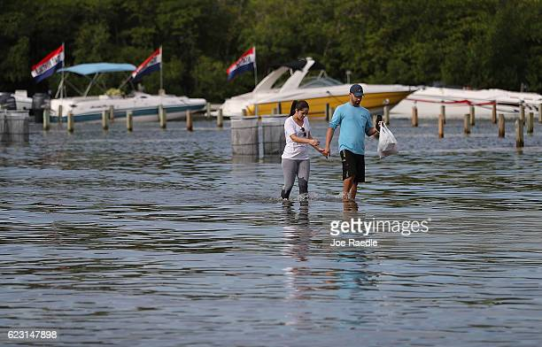 Yaneisy Duenas and Ferando Sanudo walk through the flooded parking lot to their boat at the Haulover Marine Center on November 14 2016 in North Miami...