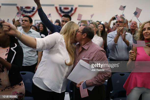 Yanet Parano orginally from Cuba hugs Romeo Rivera orginally from Guatemala after participating in a ceremony to become American citizens during a US...