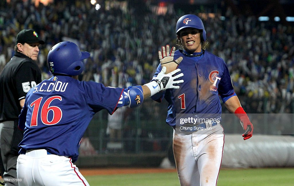 Yang Dai-Kang #1 of Chinese Taipei celebrates with his team mate Chou Szu-Chi # 16 in the third inning during the World Baseball Classic First Round Group B match between Chinese Taipei and South Korea at Intercontinental Baseball Stadium on March 5, 2013 in Taichung, Taiwan.