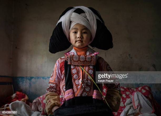 Yang Jialan of the Long Horn Miao ethnic minority group wears a headdress as she prepares before Tiaohua or Flower Festival as part of the Lunar New...
