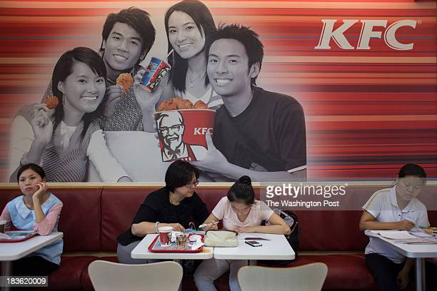 Yang Jie 42 helps her daughter Ma Qianyi 12 with her homework in a KFC restaurant between the end of her school day and the beginning of a 3 hour...