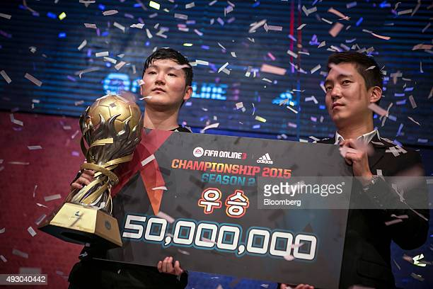 Yang Jin Hyeob left a professional videogame player accepts a cash prize from Park Jeongmu project director of Nexon Korea after winning the final...