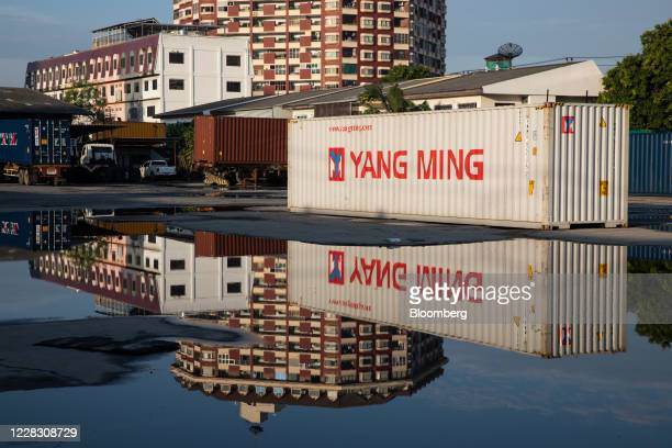 A Yang Ming Marine Transport Corp shipping container is reflected in a puddle of water at the site of a former depot in Bangkok Thailand on Wednesday...