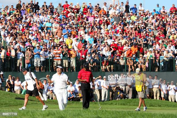 Yang of South Korea celebrates a birdie putt on the 18th green alongside Tiger Woods during the final round of the 91st PGA Championship at Hazeltine...