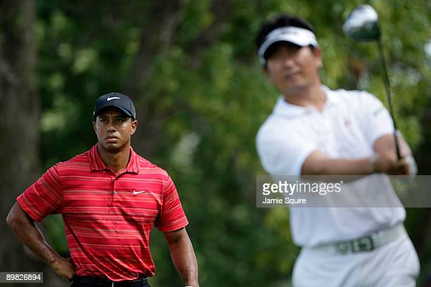 E Yang of South Korea hits his tee shot on the ninth hole as Tiger Woods looks on during the final round of the 91st PGA Championship at Hazeltine...