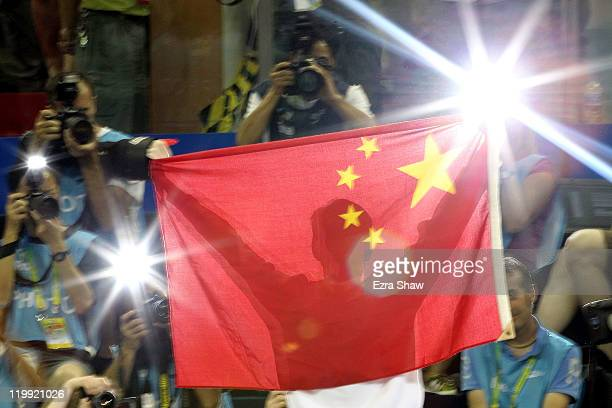 Yang Sun of China holds the Chinese flag after winning the gold medal in the Men's 800m Freestyle Final during Day Twelve of the 14th FINA World...