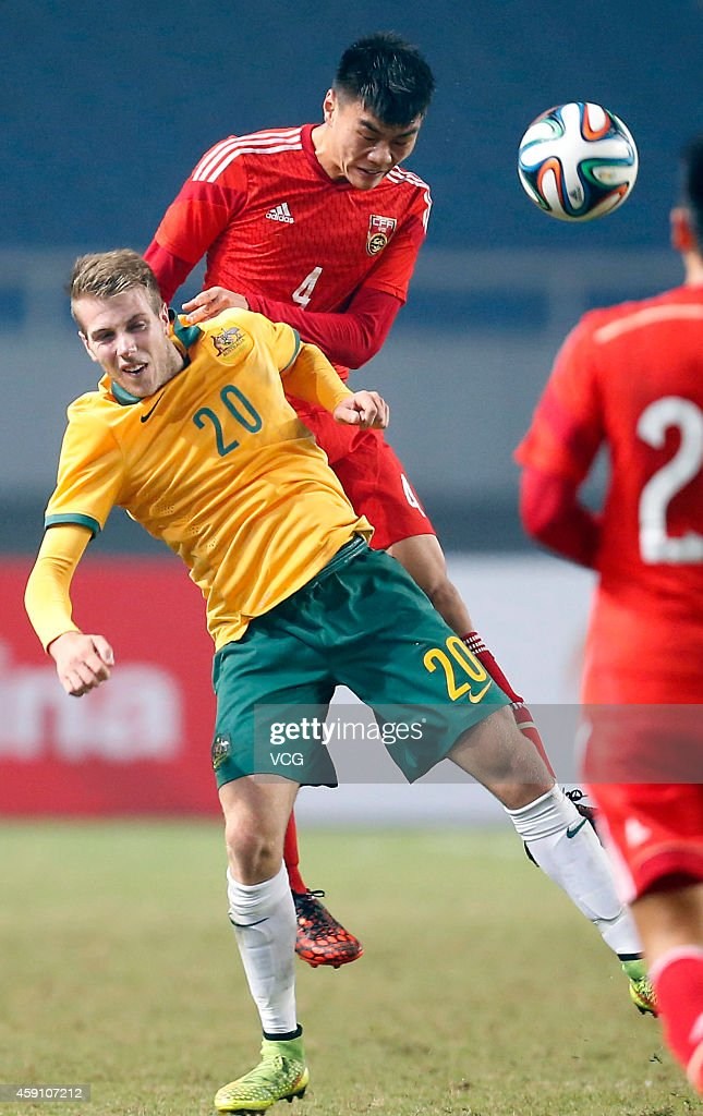 Yang Ting #4 of China and Andrew James Hoole #20 of Australia battle for the ball during the match between China U22 and Australia U22 on day three of the 'Wuhan City of Automobile' International Youth Football Tournament at Wuhan Sports Center Stadium on November 16, 2014 in Wuhan, China.