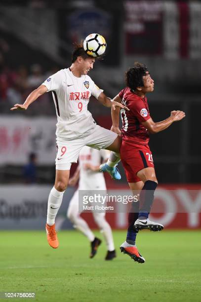Yang Xu of Tianjin Quanjian competes for the ball against Kento Misao of Kashima Antlers during the AFC Champions League Round of 16 first leg match...