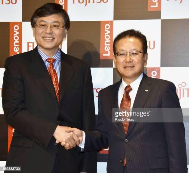 Yang Yuanqing chief executive officer of China's Lenovo Group Ltd and Tatsuya Tanaka president of Japan's Fujitsu Ltd shake hands during a press...