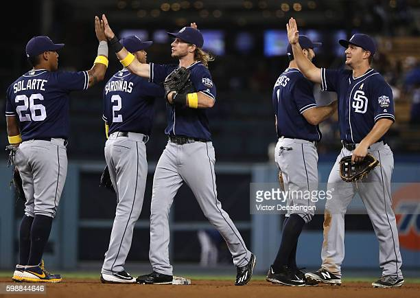 Yangervis Solarte and Travis Jankowski of the San Diego Padres and teammates celebrate with high fives after their 42 win in their MLB game against...
