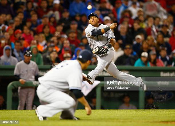 Yangervis Solarte of the New York Yankees throws to first base over his teammate Masahiro Tanaka against the Boston Red Sox during the game at Fenway...