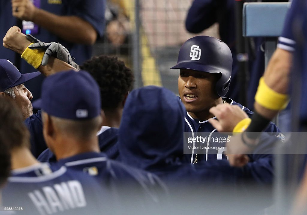 Yangervis Solarte #26 of the San Diego Padres celebrates with teammates in the dugout after hitting a solo homerun in the eighth inning during the MLB game against the Los Angeles Dodgers at Dodger Stadium on September 2, 2016 in Los Angeles, California.