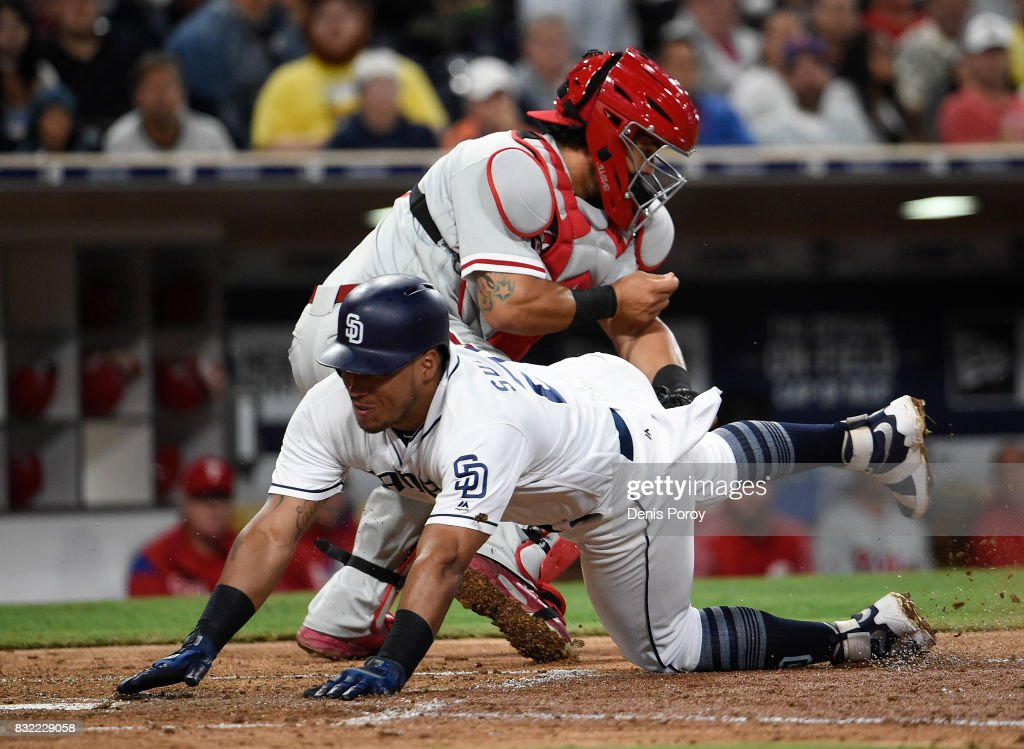 Yangervis Solarte #26 of the San Diego Padres dives as scores past the the tag of Jorge Alfaro #38 of the Philadelphia Phillies during the fifth inning of a baseball game at PETCO Park on August 15, 2017 in San Diego, California.