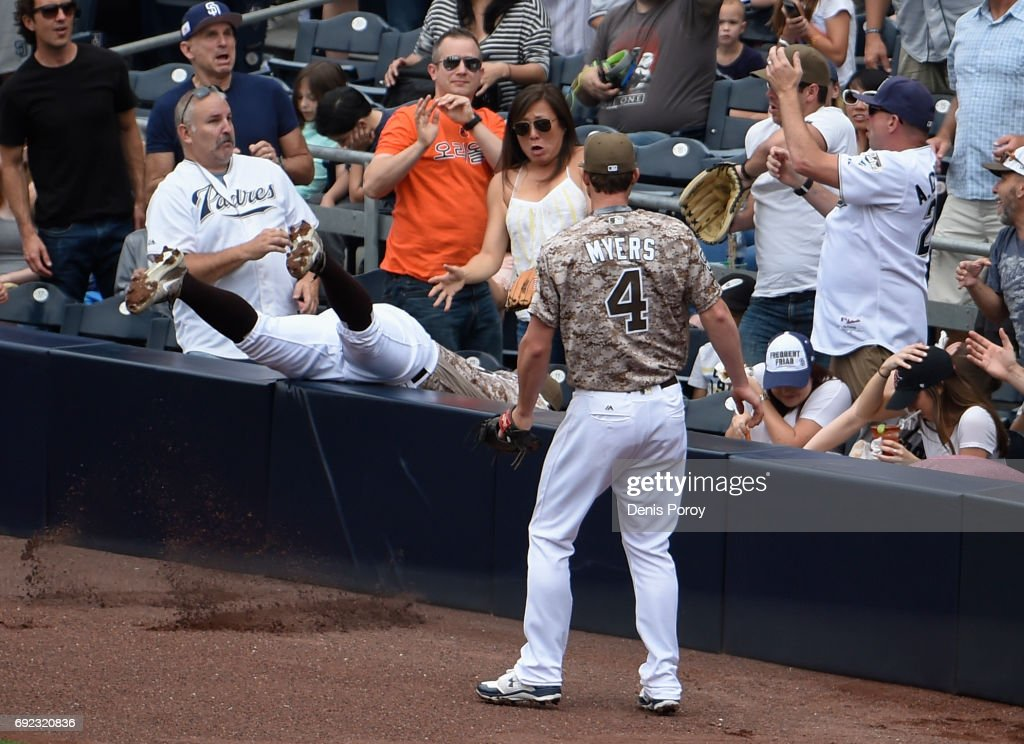 Yangervis Solarte #26 of the San Diego Padres goes into the stands after a foul ball hit by Jeff Hoffman #34 of the Colorado Rockies as Wil Myers #4 looks on during the fourth inning of a baseball game at PETCO Park on June 4, 2017 in San Diego, California. Solarte was unable to make the catch.