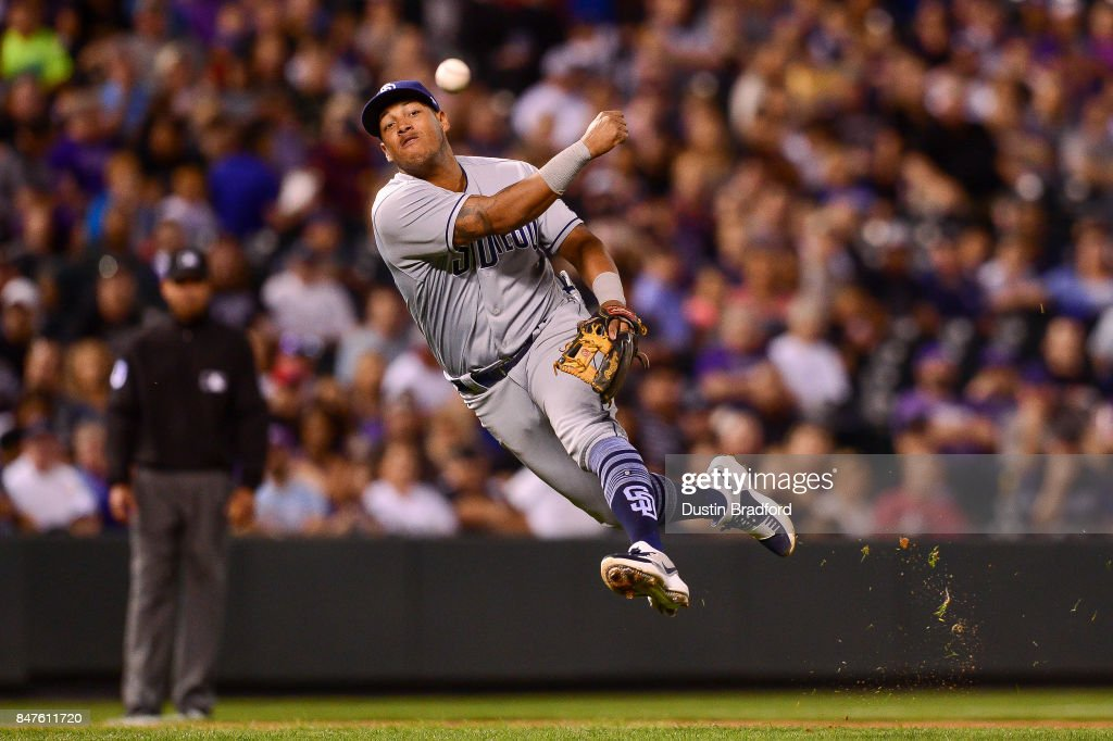 Yangervis Solarte #26 of the San Diego Padres makes a leaping throw to first base for an out after fielding a grounder barehanded against the Colorado Rockies in the sixth inning of a game at Coors Field on September 15, 2017 in Denver, Colorado.
