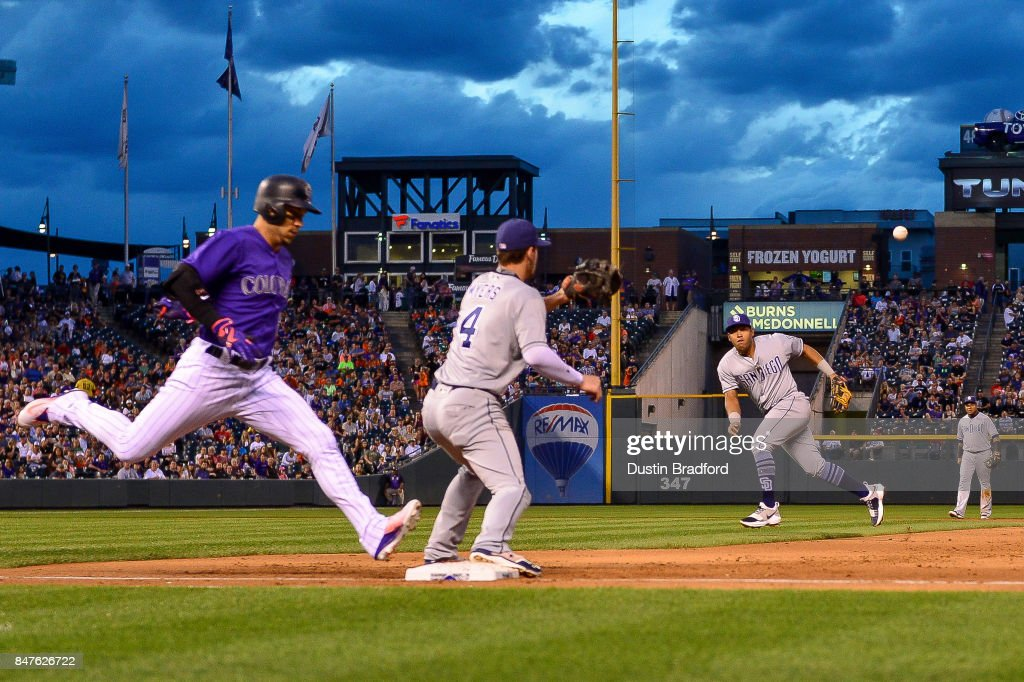 Yangervis Solarte #26 of the San Diego Padres makes an error on a throw to Wil Myers #4 while positioned in a heavy shift against Carlos Gonzalez #5 of the Colorado Rockies at Coors Field on September 15, 2017 in Denver, Colorado.