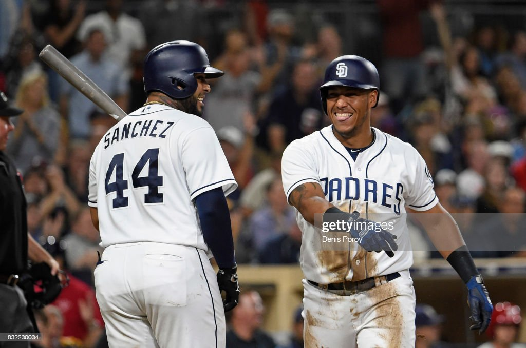 Yangervis Solarte #26 of the San Diego Padres, right, is congratulated by Hector Sanchez #44 after scoring during the fifth inning of a baseball game against the Philadelphia Phillies at PETCO Park on August 15, 2017 in San Diego, California.