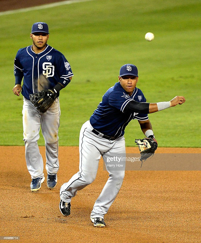 Yangervis Solarte #27 of the San Diego Padres throws out Yasiel Puig #66 of the Los Angeles Dodgers in front of Alexi Amarista #5 during the fifth inning at Dodger Stadium on August 20, 2014 in Los Angeles, California.
