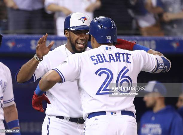 Yangervis Solarte of the Toronto Blue Jays is congratulated by Teoscar Hernandez after hitting a tworun home run in the seventh inning during MLB...