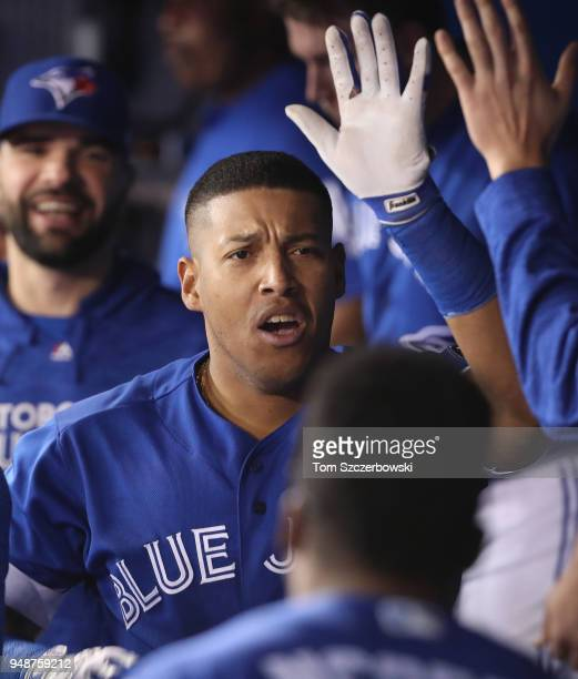 Yangervis Solarte of the Toronto Blue Jays is congratulated by teammates in the dugout after hitting a solo home run in the third inning during MLB...