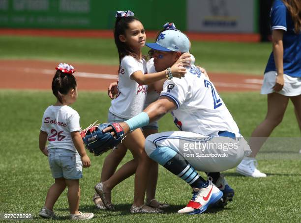 Yangervis Solarte of the Toronto Blue Jays is greeted by his daughters on Fathers Day before the start of MLB game action against the Washington...