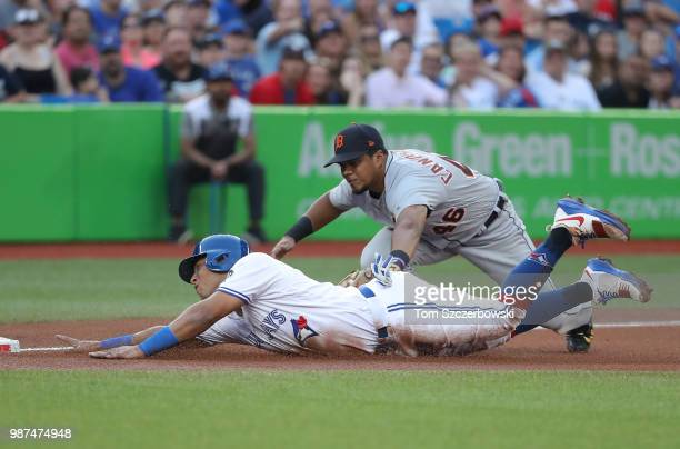 Yangervis Solarte of the Toronto Blue Jays is tagge dout by Jeimer Candelario of the Detroit Tigers as he tries to advance from first base to third...