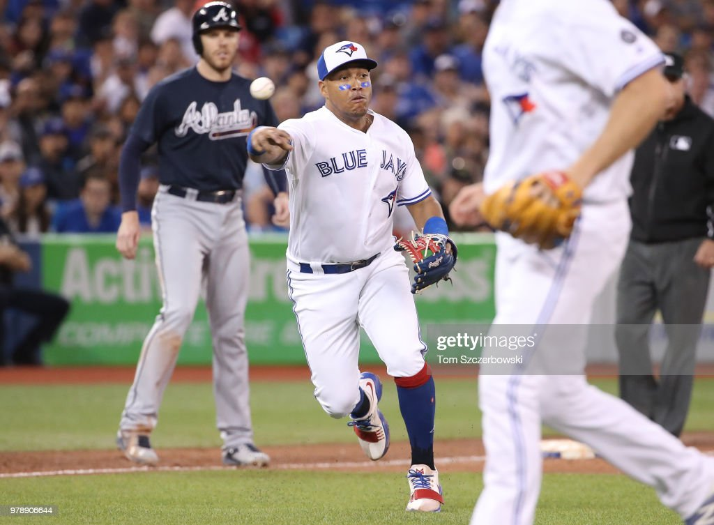 Yangervis Solarte #26 of the Toronto Blue Jays makes the play and throws out the baserunner in the sixth inning during MLB game action as Freddie Freeman #5 of the Atlanta Braves has to stay at third base at Rogers Centre on June 19, 2018 in Toronto, Canada.