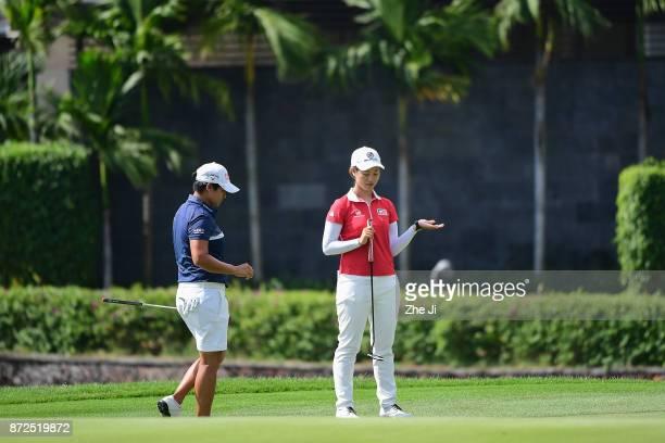 Yani Tseng of Chinese Taipei and Xiyu Lin of China play a shot on the 18th hole during the third round of the Blue Bay LPGA at Jian Lake Blue Bay...