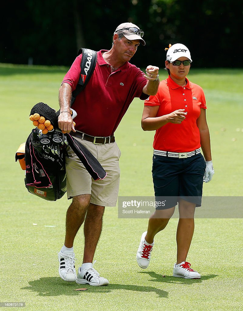 Yani Tseng of Taiwan chats with her caddie Paul Fusco during a practice round prior to the start of the HSBC Women's Champions at the Sentosa Golf Club on February 26, 2013 in Singapore, Singapore.