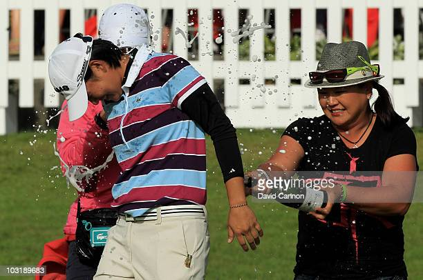 Yani Tseng of Taiwan is sprayed with champagne by Christina Kim of the USA after securing a 1 shot victory on the 18th green during the final round...