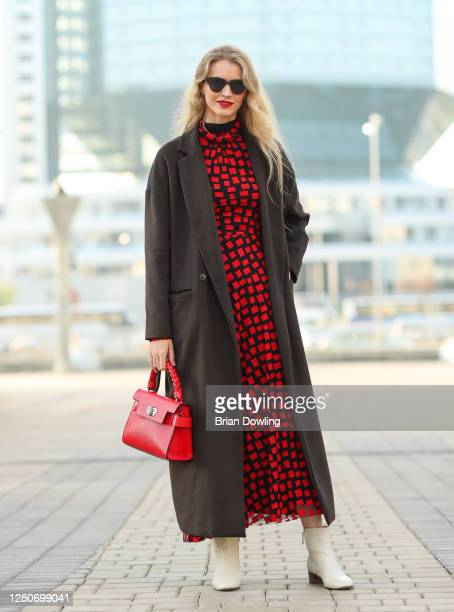 Yanina Hancharova seen wearing a dark gray jacket by Lakbi, a black a red dress by Nikolia Morozov, white leather boots and a red leather bag by...