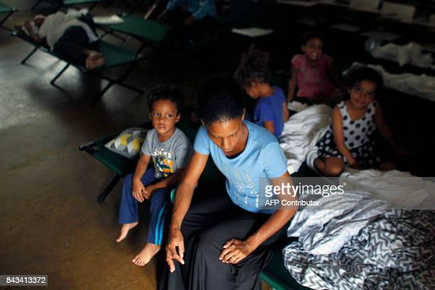 Yanina Lopez sits on a folding bed surrounded by her children at an emergency center Hurricane Irma approaches Puerto Rico in Fajardo on September 6...