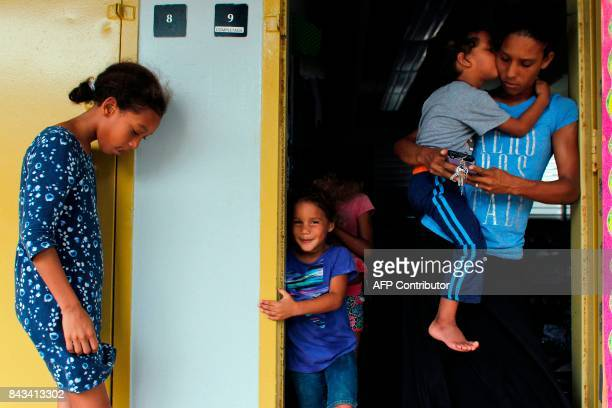 Yanina Lopez stand is surrounded by her children at an emergency center as Hurricane Irma approaches Puerto Rico in Fajardo on September 6 2017 Irma...