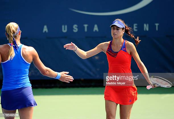 Yanina Wickmayer of Belgium taps hands with her partner Sorana Cirstea of Romania during their women's doubles first round match against Casey...