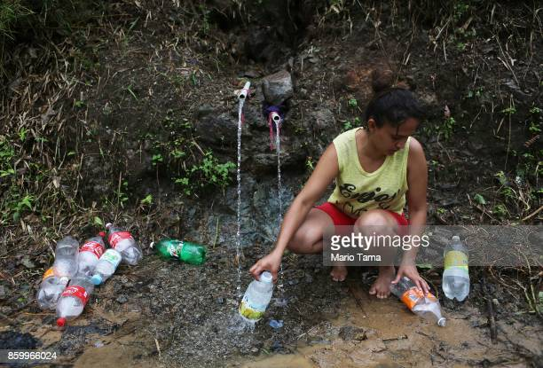 Yanira Rios collects spring water for use in her house which is without running water or electricity nearly three weeks after Hurricane Maria hit the...