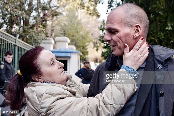 Yanis Varoufakis is greeetd by a well wisher as he arrives at the Presidential Palace to be sworn in as the Finance Minister under the country's new...