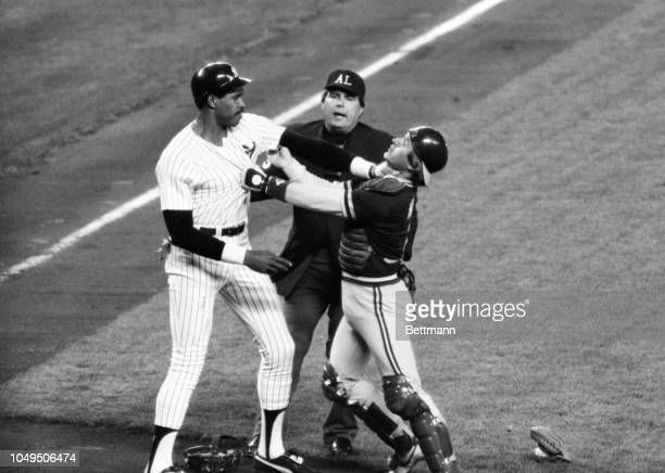 Yankee Dave Winfield grabs Oakland catcher Mike Heath by the throat as they fought in front of the mound when Winfield objected to a knock down pitch...